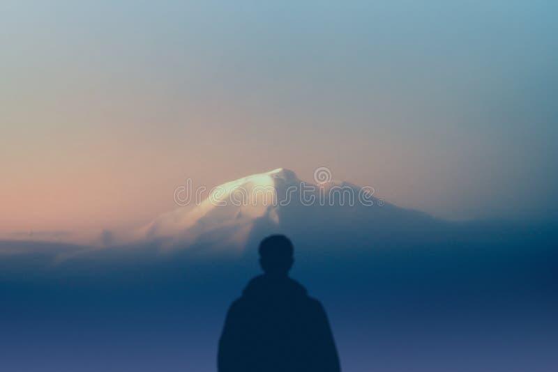 Mankonturfotvandraren står hållande ögonen på det utomhus högsta berget på solnedgången begreppsnatur och människosläkte kopiera  royaltyfri bild