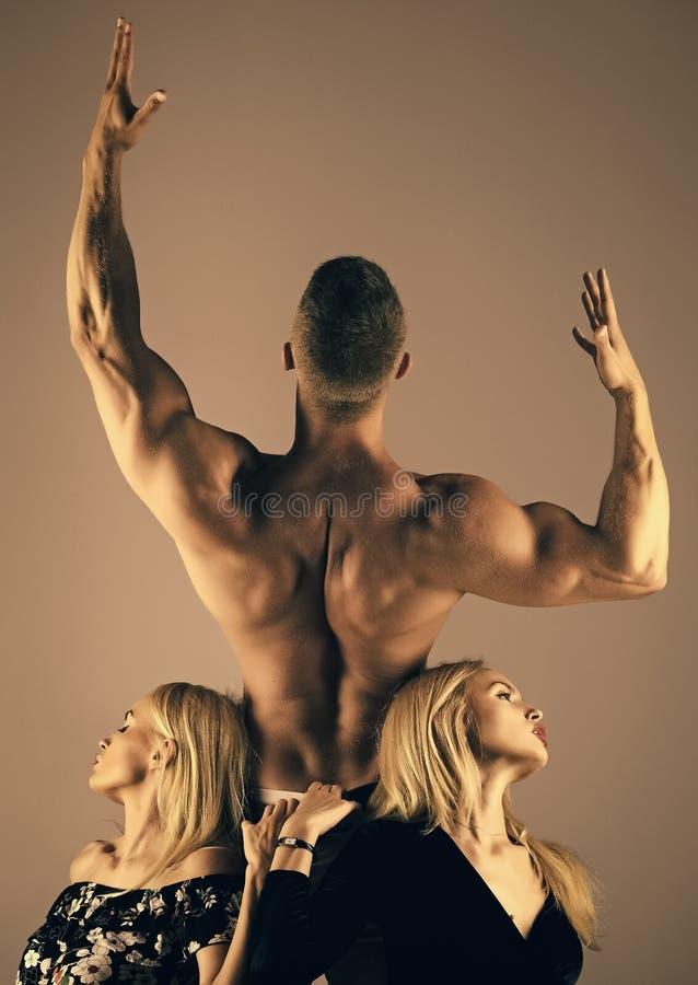 Mankroppsbyggare med muskulösa tillbaka lönelyfthänder och flickor arkivfoton