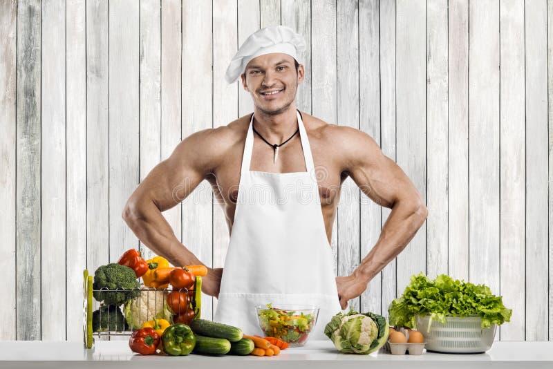 Mankroppsbyggare på kök arkivfoton