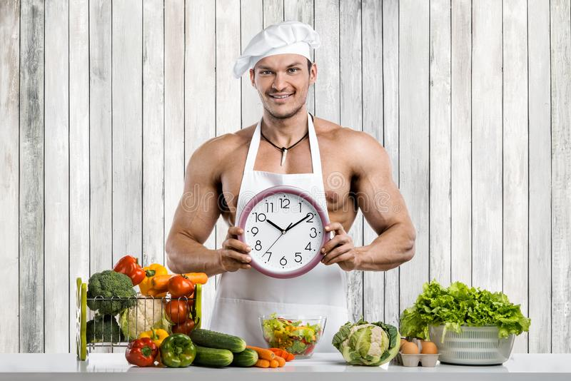 Mankroppsbyggare som lagar mat på kök arkivbilder