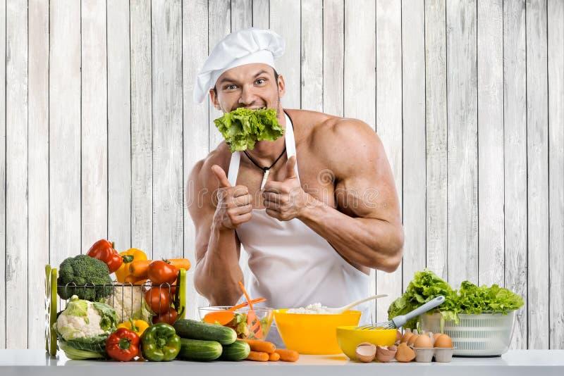 Mankroppsbyggare som lagar mat på kök arkivbild