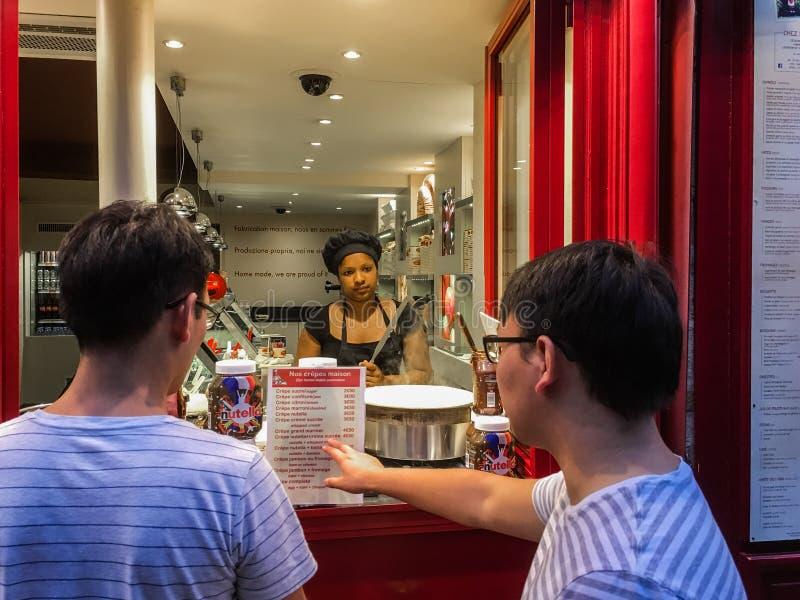 Mankunder väljer menyobjektet på kräppställningen i Paris royaltyfri fotografi