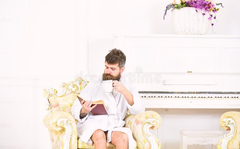 Manläsebok, medan dricka kaffe eller te Rikt grabbsammanträde i antik fåtölj Tycka om perfekt dag royaltyfri fotografi