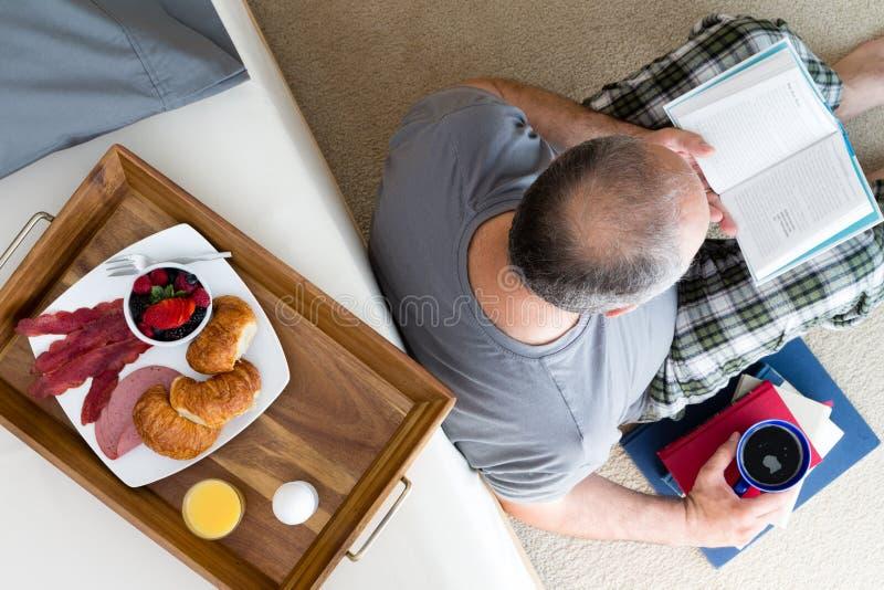 Manläsebok och tycka omkaffe och frukost arkivfoton