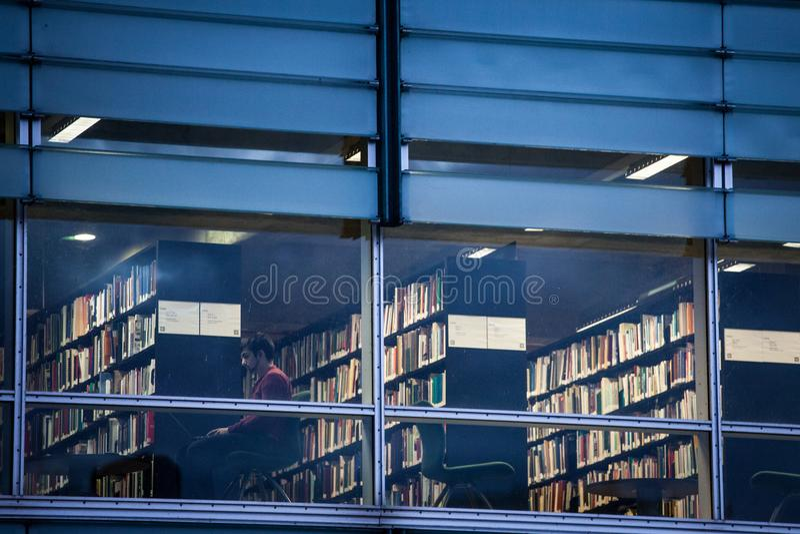 Manläsning på hans bärbar dator i ett av rummen av det Montreal arkivet, kallade också Bibliotheque och arkivnationales du Quebec royaltyfri foto