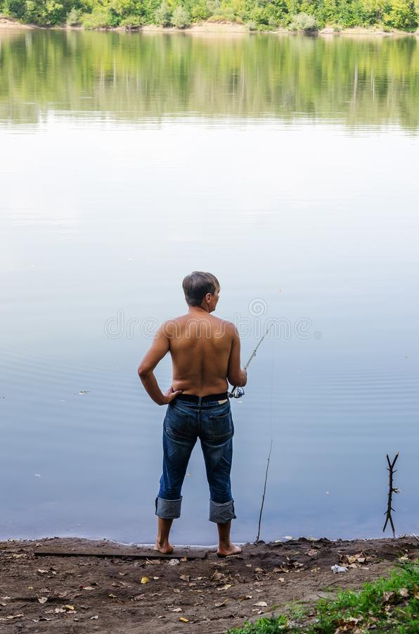 Manlås fiskar på en fiskepol, på kusten av en sjö arkivbild