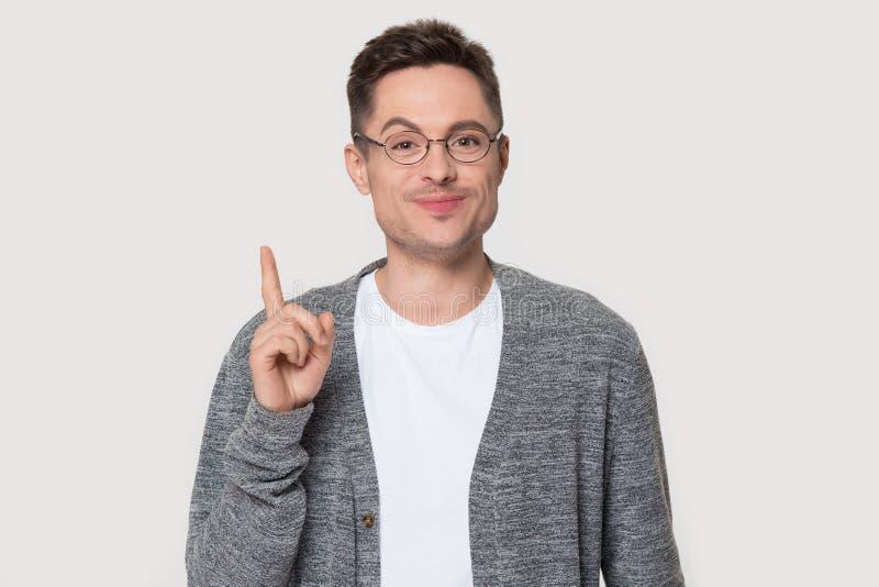 Manlönelyftfingret uppfinner upp idé poserar på den gråa väggen royaltyfri foto