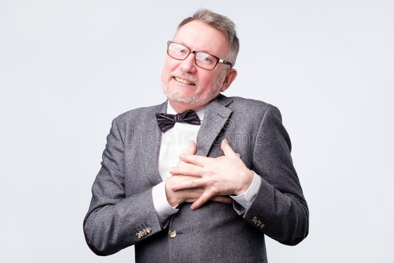 Manleenden lyckligt, håller händer på bröstkorg, uttrycker hans positiva sinnesrörelser arkivbilder