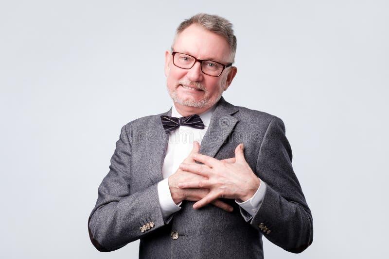 Manleenden lyckligt, håller händer på bröstkorg, uttrycker hans positiva sinnesrörelser arkivfoto