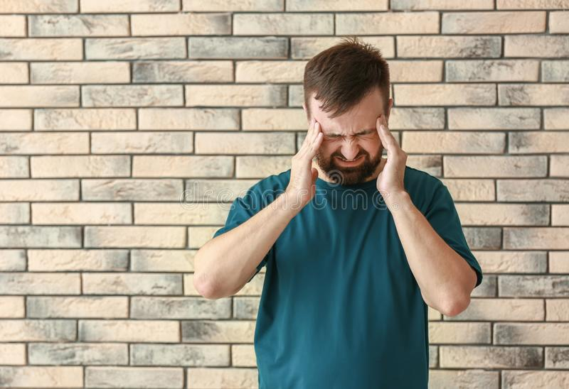Manlidande från huvudvärk mot tegelstenväggen royaltyfria bilder