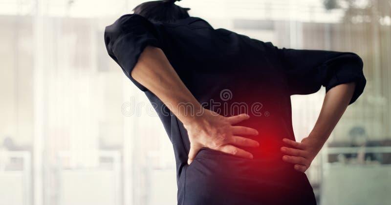 Manlidande från tillbaka smärtar orsak av kontorssyndrommen, hans händer som trycker på på lägre baksida Läkarundersökning- och h royaltyfri foto
