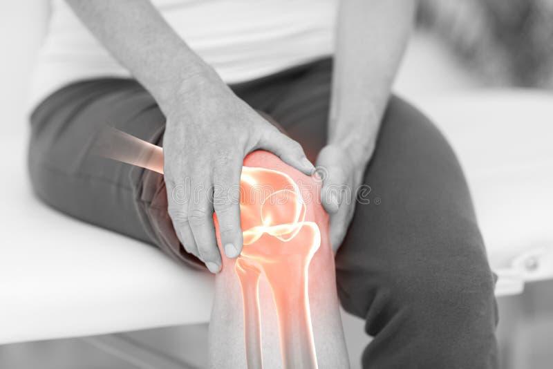 Manlidande med knäet smärtar royaltyfria bilder