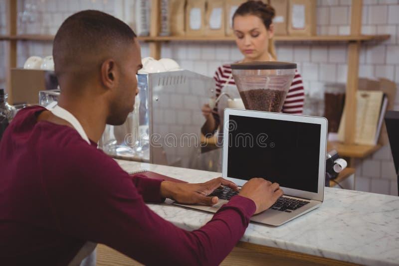 Manlig ägare som använder bärbara datorn i kafé arkivfoto