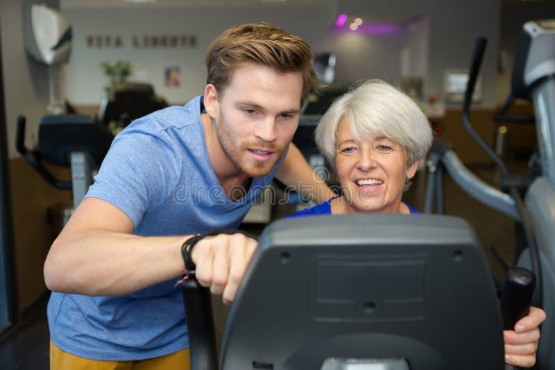 Manlig äldre kvinnas för instruktörinställning maskin för övning royaltyfri foto