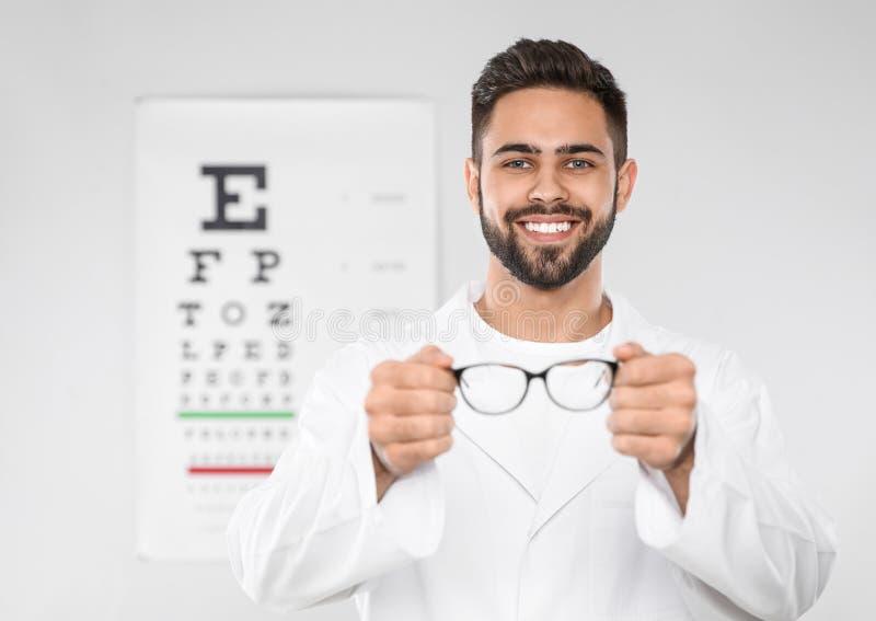 Manlig ögonläkare med glasögon i klinik arkivfoto
