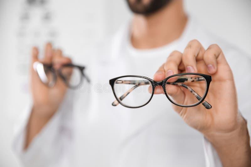 Manlig ögonläkare med glasögon i kliniken, closeup arkivfoto