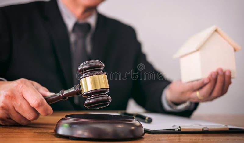 Manlig advokat- eller domarehand` s som slår auktionsklubban på att låta kvarteret arkivbilder