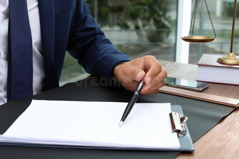Manlig advokat som arbetar med dokument på tabellen royaltyfria bilder