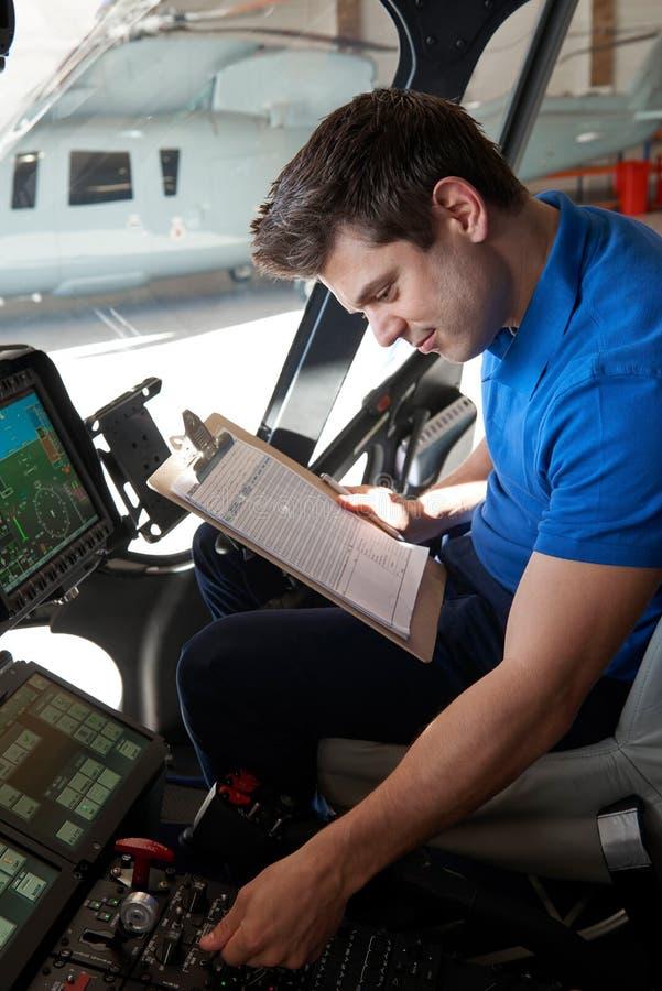 Manlig Aero tekniker With Clipboard Working i helikoptercockpit arkivbilder