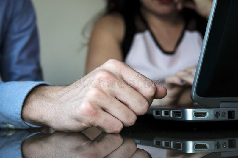 Manlig affärshand och kvinna som tillsammans arbetar på hemmastatt kontor för bärbar dator royaltyfria bilder