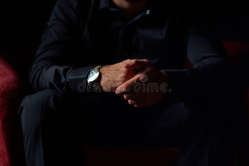 Manlig affärsman i en svart dräkt som sitter i röd stol, svart bakgrund, inga synliga framsidor, studioskytte royaltyfri foto