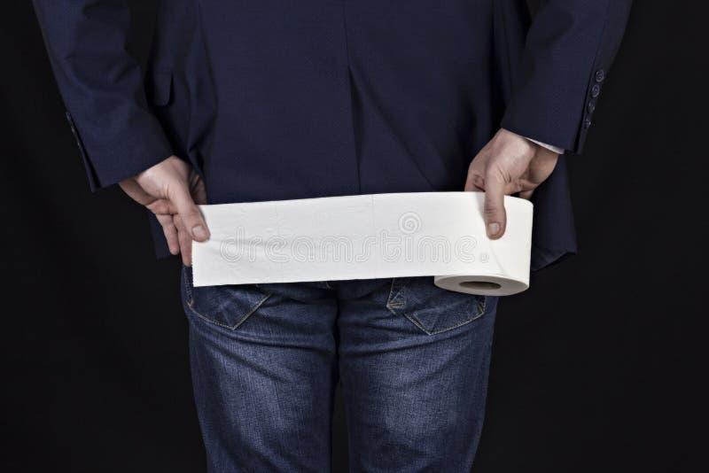 Manlig affärsman som rymmer ett stycke av toalettpapper, svart bakgrund royaltyfri bild