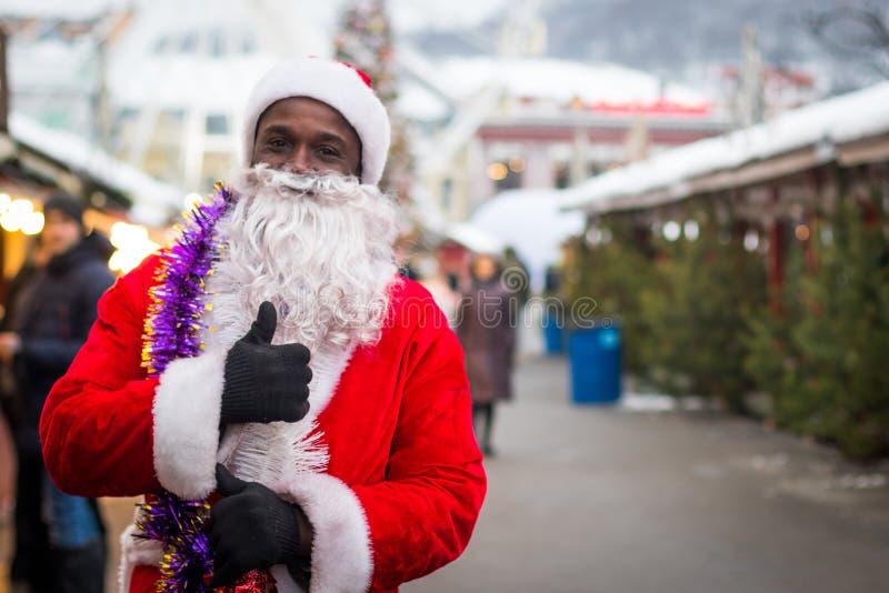 Manlig afrikansk amerikan som kläs som Santa Claus på julmässan fotografering för bildbyråer