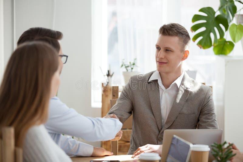 Manlig anställd för Millennial affärsmanhandskakning på förhandsmöte arkivbild