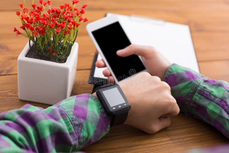 Manlig användande smart klocka på arbetsplatsen, slut upp, sidosikt, fotografering för bildbyråer