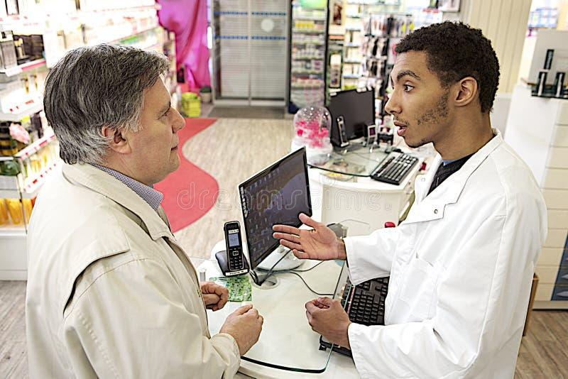 Manlig apotekare för ung mulatt som talar med en kund royaltyfri fotografi