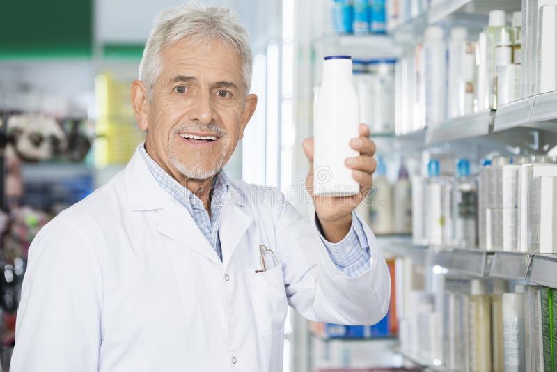 Manlig apotekare Holding Shampoo Bottle i apotek royaltyfria foton