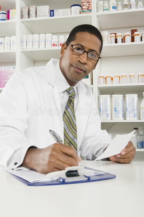 Manlig apotekare som arbetar i apotek royaltyfria bilder
