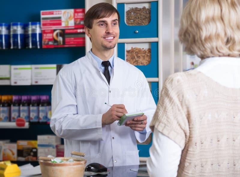 Manlig apotekare som talar till kunden på apotek arkivbild