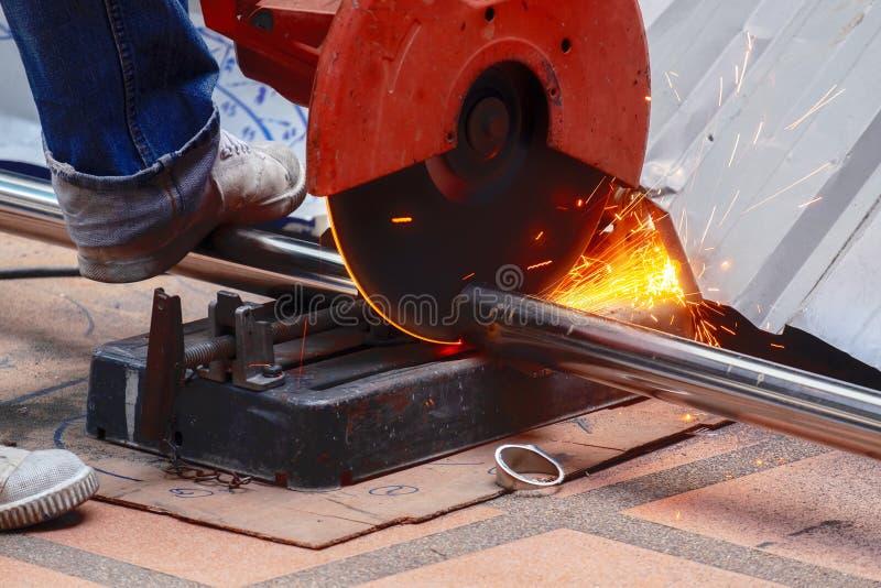 Manlig arbetarbrukskotlett såg till att klippa ett tjockt rostfritt stålrör fotografering för bildbyråer
