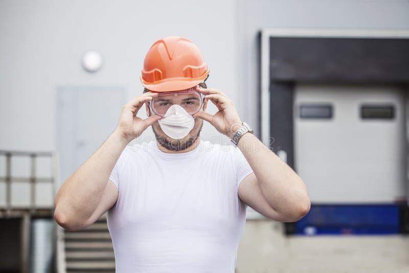 Manlig arbetare för byggmästare i skyddande maskering och exponeringsglas i hjälmen arkivbilder