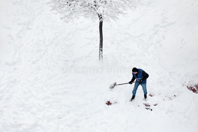 Manlig arbetare, i att skyffla för likformig som är insnöat gården efter en snöstorm i vinter arkivfoto