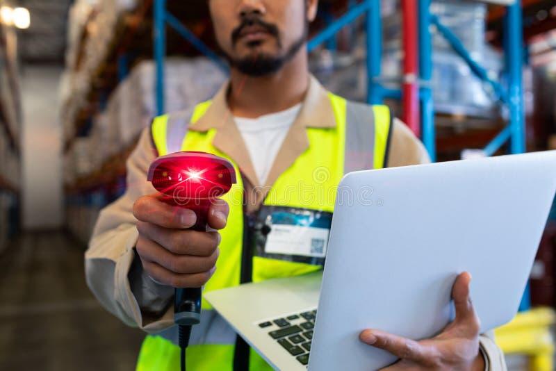Manlig arbetare med bildläsaren för bärbar datorvisningbarcode på kamera i lager fotografering för bildbyråer