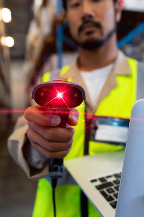 Manlig arbetare med bildläsaren för bärbar datorvisningbarcode på kamera i lager arkivbild