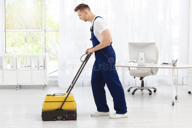 Manlig arbetare med golvlokalvårdmaskinen royaltyfria bilder