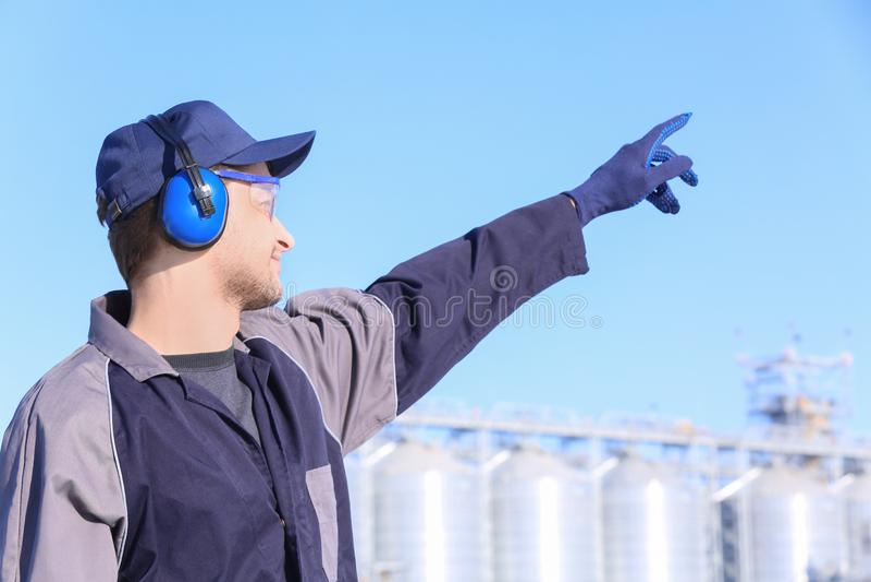 Manlig arbetare med hörlurar utomhus arkivbild