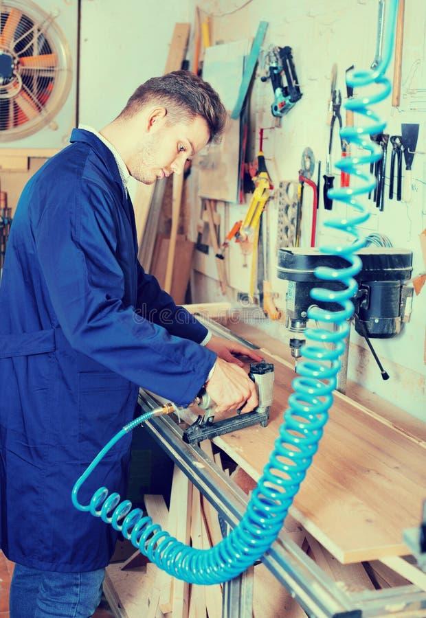Manlig arbetare som arbetar med malningskäraren på seminariet arkivbilder