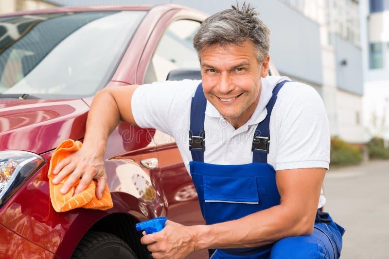 Manlig arbetare som gör ren den röda bilen arkivfoto