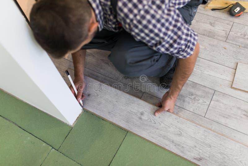 Manlig arbetare som installerar laminatdurken, man som installerar den nya trälaminatdurken Man som lägger laminaten som hemma dä arkivfoton