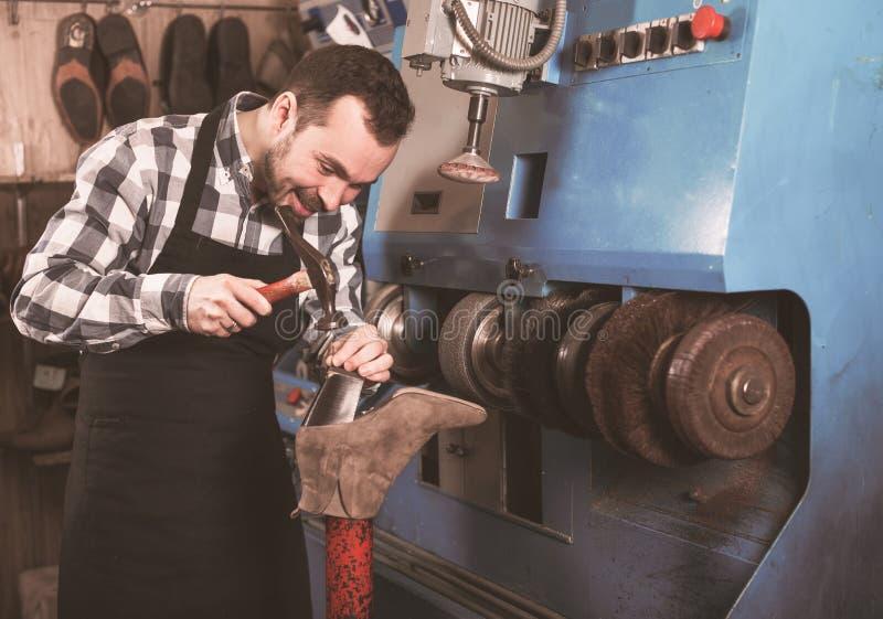 Manlig arbetare som reparerar skon arkivfoto