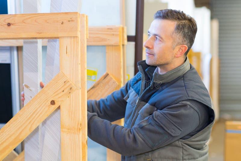 Manlig arbetare som staplar material i träskärmram arkivbilder
