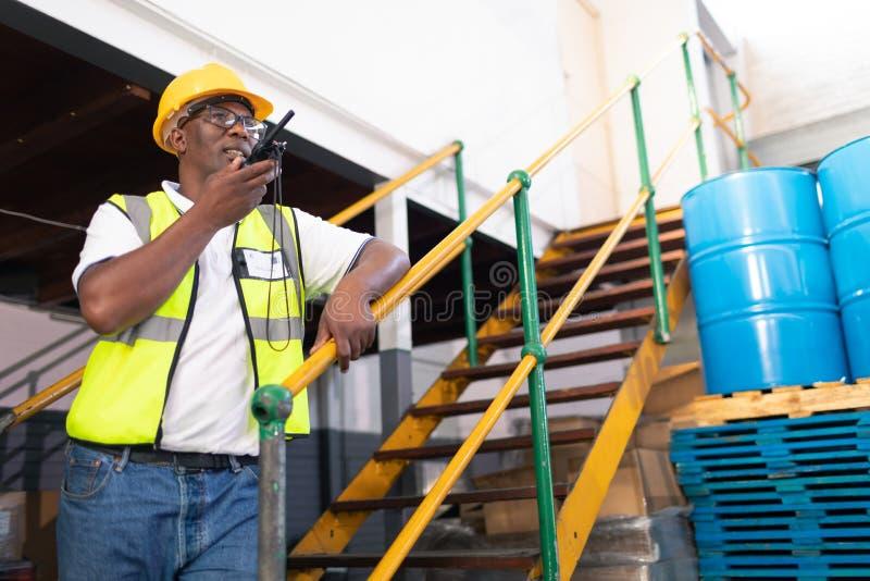 Manlig arbetare som talar på walkietalkie i lager arkivfoton