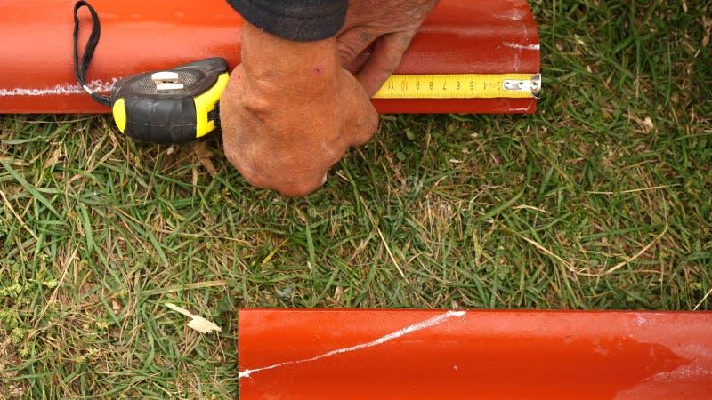 Manlig arbetares hand som mäter rött stål som utomhus taklägger stycken gem Närbild av material och utrustningar för hushåll fotografering för bildbyråer