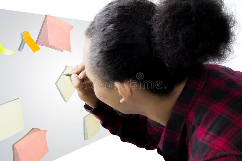 Manlig arbetarhandstil på en självhäftande anmärkning royaltyfria foton