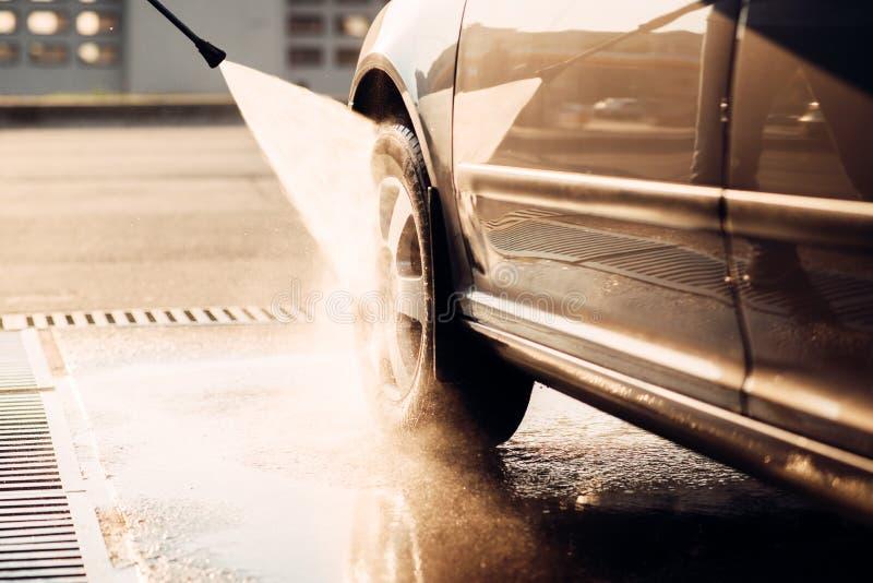 Manlig arbetarwash bilen med högtryckpackningen arkivfoto
