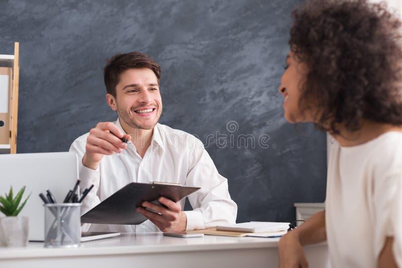 Manlig arbetsgivare som intervjuar kvinnan i hans kontor royaltyfri fotografi